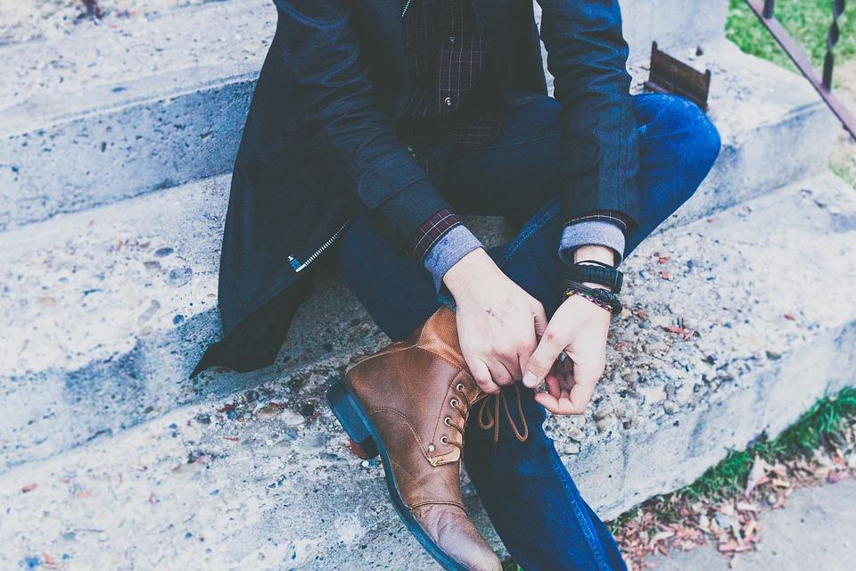 Jeune homme habillé avec une tenue chic composée d'un jean, d'une chemise d'une veste et de bottines en cuir