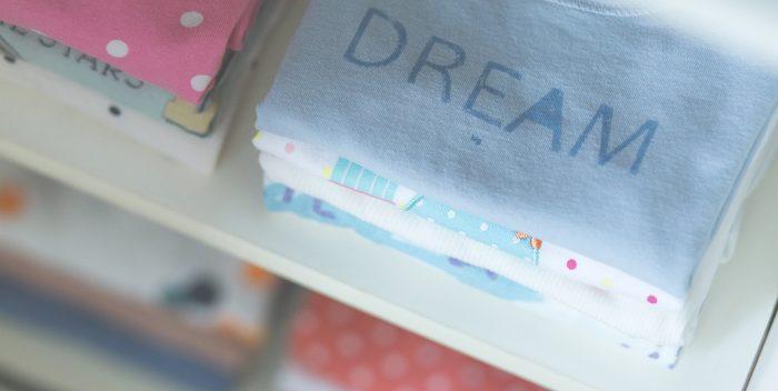 Piles de vêtements pour bébé dans un placard