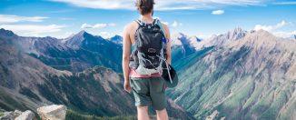 Randonneur qui admire un paysage de montagne sur le bord d'une falaise