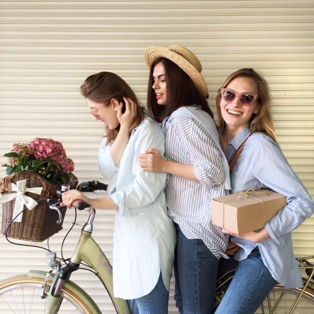 3 jeunes femmes posant sur un vélo avec des fleurs et un colis