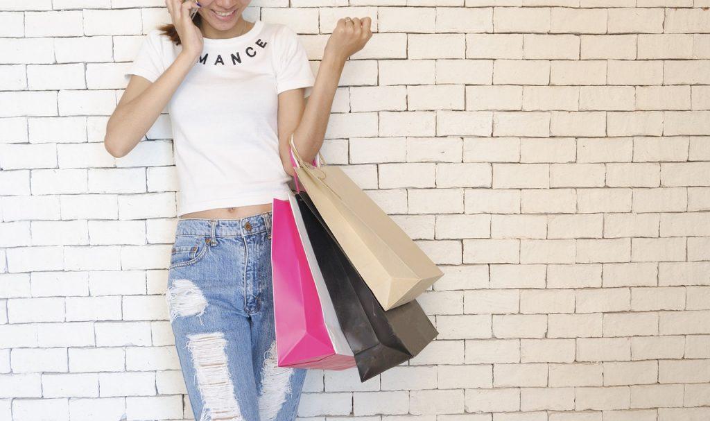 femme portant des sacs de shopping portant un jean et un t shirt blanc devant un mur en briques blanches